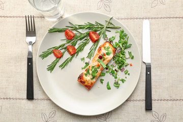Plate with salmon, herbs, glass and flatware on light table