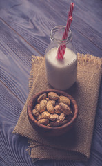 lmond milk in bottles with almond nuts on wooden background