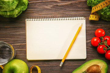 Empty notebook and set of healthy food on wooden table