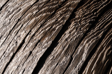 The texture is an old dark wooden board with a deep crack and shallow depths