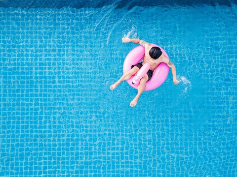 Top view, a man relaxing on pink flamingo swim pool float, on swimming pool in summer