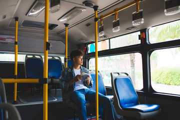 Young man sitting in city bus and reading a book.