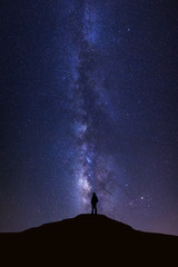 Landscape with milky way, Night sky with stars and silhouette of man standing on high moutain