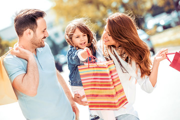 Smiling parents and daughter with shopping bags .