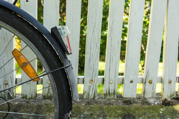 back wheel of bicycle in front of white fence