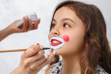 Artist doing clown makeup for a little girl