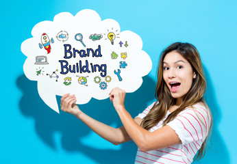 Brand Building text with young woman holding a speech bubble on a blue background