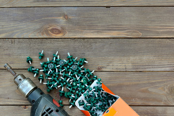 Roofing screws and a drill on a wooden table. The view from the top. Template for labor day .Roofer, roofing work.