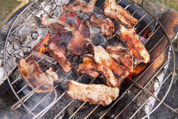Bacon being grilled, outdoors