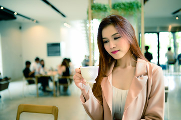 Portrait of beautiful woman holding a cup of coffee in her hand in blur background coffee shop, she drink coffee in the morning, vintage style