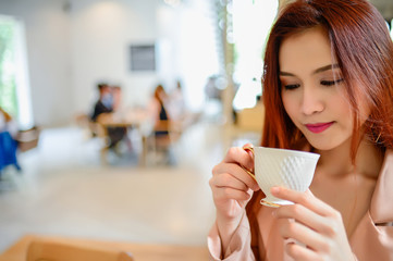 Portrait of beautiful woman and holding a cup of coffee in her hand in blur background coffee shop, she drink coffee in the morning