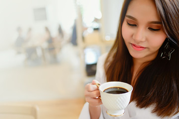 Portrait of beautiful woman holding a cup of coffee in her hand in blur background coffee shop, she drink coffee in the morning, with copy space for text