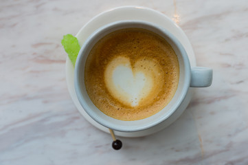 A cup of coffee with heart pattern in a white cup on white marble background and green sugar stick, latte coffee