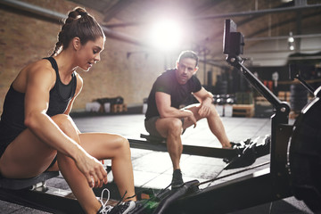 Two sportsmen preparing to workout rowing machines