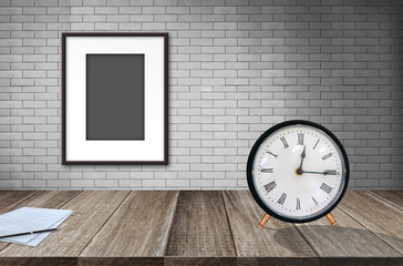 Blank photo frame on old brick wall and paper and vintage alarm clock