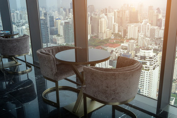 Two Modern Chair and circle glass table on tower office room with urban skyline background.