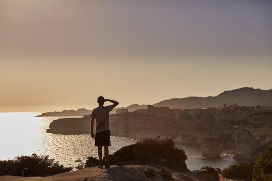 Ragazzo guarda l'orizzonte al tramonto a Bonifacio