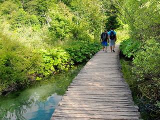 Ragazzi passeggiano nel parco nazionale dei laghi di Plitvice lungo un ponticello di legno immersi nella natura e con cielo riflesso nell'acqua