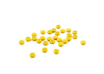Pills stock images. Yellow pills on a white background. Smileys photo