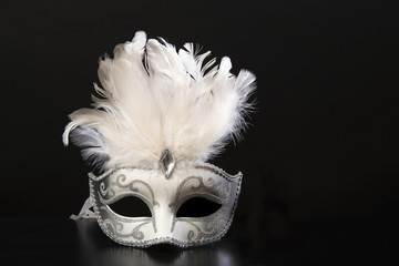 Pretty white and silver venetian carnival mask with feathers on a black background