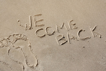 We come back - written by hand in sand on a sea beach, with a soft wave. End of rest, holiday.