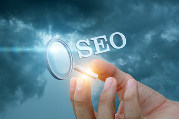Hand showing seo on a blue background.