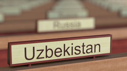 Uzbekistan name sign among different countries plaques at international organization. 3D rendering