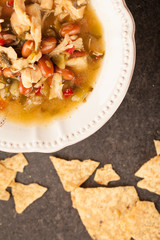 White chicken chili with red peppers, chicken, and beans in white bowl with corn tortilla chips top view