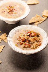 White chicken chili with red peppers, chicken, and beans in white bowl with corn tortilla chips vertical shot