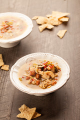 White chicken chili with red peppers, chicken, and beans in white bowl with corn tortilla chips slightly above shot