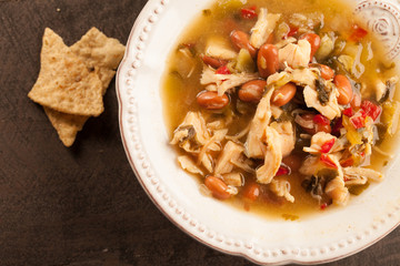 White chicken chili with red peppers, chicken, and beans in white bowl with corn tortilla chips close up shot