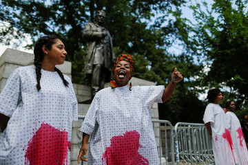 Women paint their bodies in red as they take part in protest against white supremacy in front of J. Marion Sims statue in New York