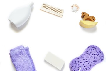 Flat lay bath products/ Shampoo, purple towel, comb, soap, wooden horse and sponge on a white background. Mockup, free space for text