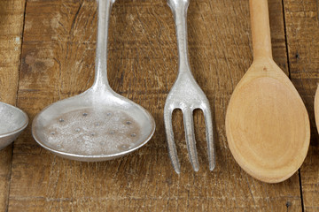 Wooden cutlery and cast aluminum cutlery on rustic wooden table