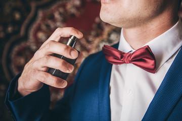 The man sprinkles himself on perfume