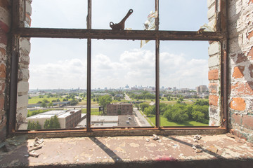 Looking out the window of an abandoned window towards the skyline of Detroit