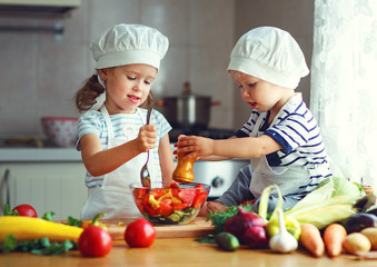 Healthy eating. Happy children prepares  vegetable salad in kitchen