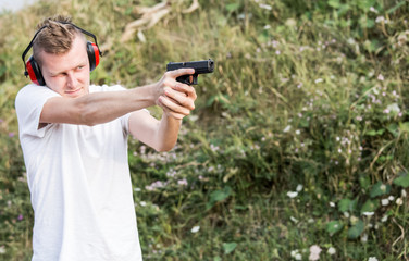 Young handsome blonde guy training policeman special forces shooting with the glock pistol gun at target with hands and protective gear in the nature in sunny day