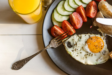 Fried eggs with tomatoes and cucumbers on a rustic wooden background