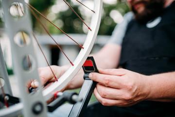 Bicycle mechanic hands repair wheel closeup