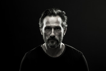 Monochrome portrait of mid aged lonely man. Black and white photo of male in black t-shirt on dark backdrop.