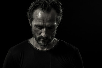 Monochrome portrait of lonely mature man on black backdrop. View of man sadly looking down.