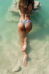 Sexy sporty tanned girl in a bikini laying in crystal clear water outdoor. Paradise beach vacation.