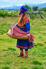 Northern Norway, a traditional dressed Sami woman with a cradle