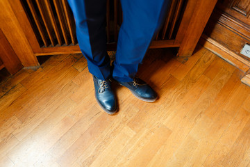 The man in the blue suit legs closeup shoes. low angle view of a person leg wearing pants