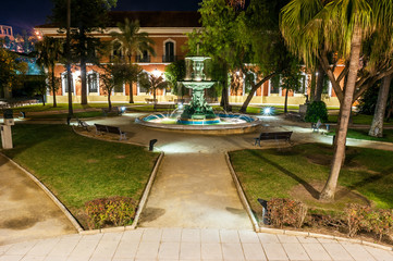 Night view of the courtyard with the central source of the public house Colon in Huelva