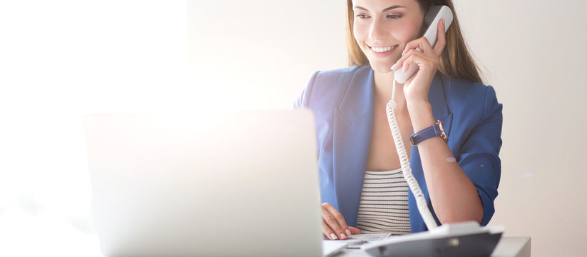 Portrait of a young woman on phone in front of a laptop computer
