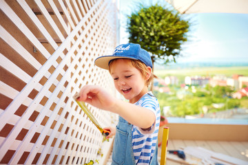 cute happy boy helping to set up a trellis on patio