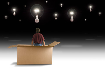 A man is standing in a box looking up at a sky filled with idea lightbulbs representing thinking outside the box, creativity, innovation and business strategy ideas.