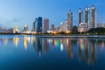 Twilight tone, City office and apartment building with water reflection in public park, Bangkok Thailand